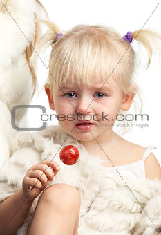 Little crying girl with a candy on white