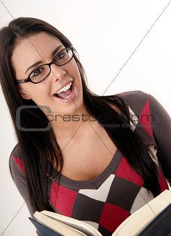 Beautiful Female Student Studies her Textbook Wearing Eyeglasses