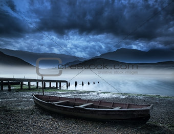 Old boat on lake of shore with misty lake and mountains landscap