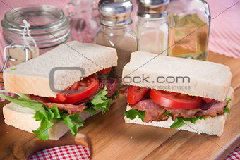Fresh BLT on white sandwich in rustic kitchen setting