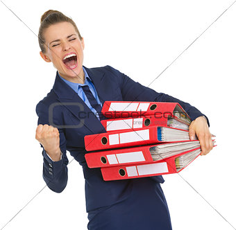 Smiling business woman with stack of documents making fist pump