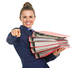 Happy business woman with stack of documents pointing in camera