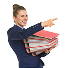 Happy business woman with stack of folders pointing on copy spac