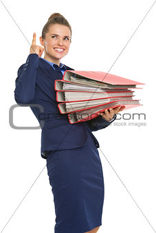 Smiling business woman with stack of folders pointing on copy sp