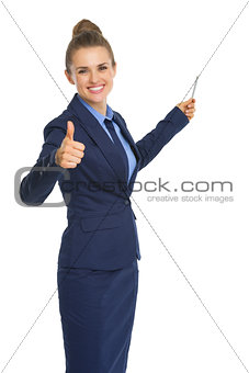 Smiling business woman pointing on copy space with pen and showi