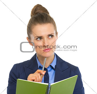 Portrait of thoughtful business woman with notepad