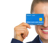 Closeup on business woman holding credit card in front of face