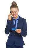 Happy business woman with credit card talking cell phone