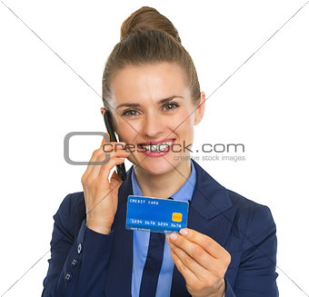 Portrait of smiling business woman with credit card talking cell