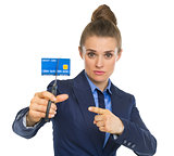 Business woman pointing on credit card squeezed in scissors
