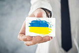 Ukrainian Businessman holding business card with Ukraine Flag