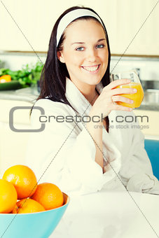 Smiling woman with orange juice in the kitchen