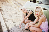 Two sad beautiful blonde girls sitting near broken car and waiting for help