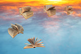 books fly over sunset clouds