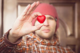 Heart shape love symbol in man hand with face on background Valentines Day romantic greeting people relationship concept winter holiday