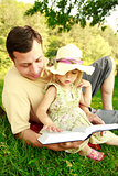 young father with his little daughter reading