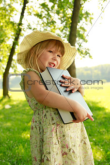 beautiful little girl with the Book in nature