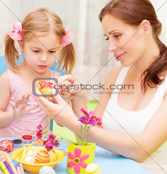 Baby girl with mother paint Easter eggs