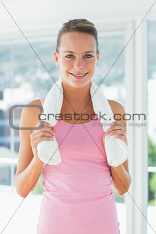 Portrait of a young woman with towel in gym
