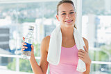 Woman with towel and water bottle in gym