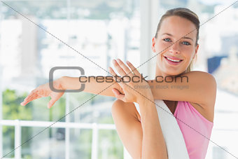 Sporty young woman stretching hands at yoga class