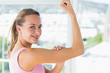 Young woman flexing muscles in gym