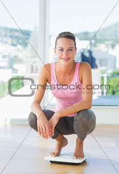 Woman crouching on weighing scale in gym
