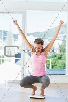 Sporty young woman crouching on weighing scale in gym