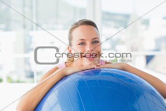 Smiling fit woman with exercise ball at gym