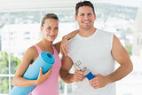 Fit couple holding water bottle and exercise mat in exercise room
