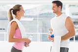 Fit couple holding water bottles and towels in exercise room