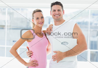 Portrait of a fit couple holding weighing scale