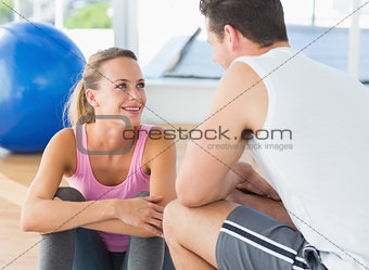 Smiling fit couple chatting in exercise room