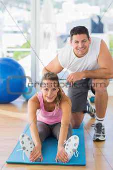 Male trainer assisting young woman with pilate exercises