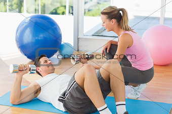 Female trainer looking at young man exercise in gym