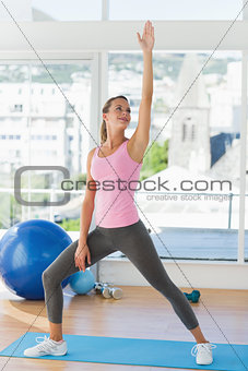 Sporty young woman stretching hand in fitness studio