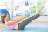 Sporty young woman stretching body in fitness studio