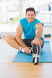 Sporty man stretching hand to leg in fitness studio