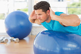 Young man exercising on fitness ball at a bright gym