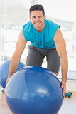 Smiling man exercising with fitness ball at gym