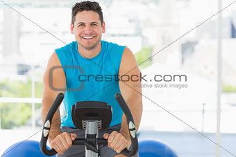 Smiling young man working out at spinning class