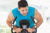 Serious man working out at spinning class