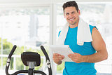 Smiling trainer with clipboard in gym