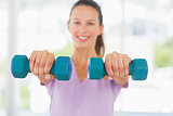 Smiling woman lifting dumbbell weights in a bright gym