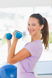 Side view of a smiling woman lifting dumbbell weights