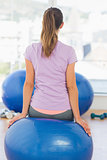 Fit young woman sitting on exercise ball at gym