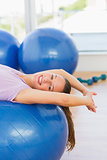 Smiling fit woman lying on exercise ball at gym
