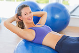 Side view portrait of a smiling fit woman lying on exercise ball