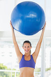 Smiling fit young woman holding up fitness ball