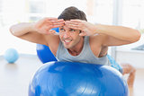 Happy fit man stretching on exercise ball